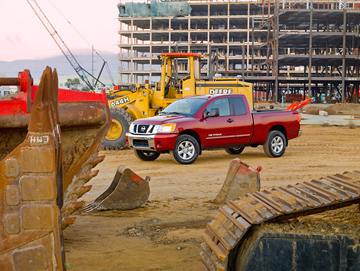 AUT 14 RK1428 01 © Kimball Stock 2009 Nissan Titan 4x4 SE Pickup Truck Red 3/4 Front View On Dirt By Construction Equipment