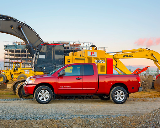 AUT 14 RK1435 01 © Kimball Stock 2009 Nissan Titan 4x4 SE Pickup Truck Red Profile View On Dirt By Construction Equipment