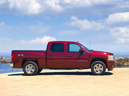 AUT 14 RK1483 01 © Kimball Stock 2010 Chevrolet Silverado Hybrid Red Profile View By Ocean