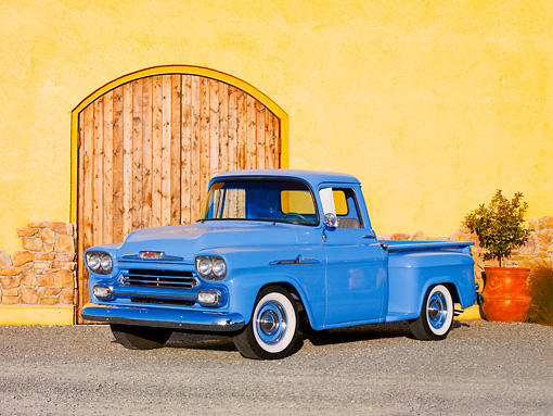 AUT 14 RK1534 01 © Kimball Stock 1958 Chevrolet Apache Pickup Truck Blue 3/4 Front View On Gravel By Building