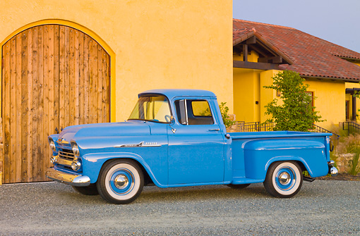 AUT 14 RK1538 01 © Kimball Stock 1958 Chevrolet Apache Pickup Truck Blue 3/4 Front View On Gravel By Building