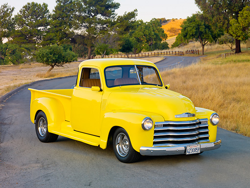 AUT 14 RK1556 01 © Kimball Stock 1950 Chevrolet Pickup Truck Yellow 3/4 Front View On Road By Hills