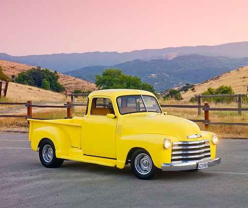 AUT 14 RK1557 01 © Kimball Stock 1950 Chevrolet Pickup Truck Yellow 3/4 Front View On Pavement By Hills
