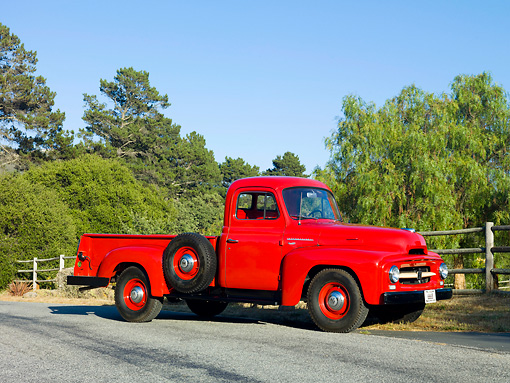 AUT 14 RK1562 01 © Kimball Stock 1954 International R110 Heavy Duty 1/2 Ton Pickup Truck Red 3/4 Front View On Pavement By Trees