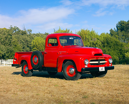 AUT 14 RK1563 01 © Kimball Stock 1954 International R110 Heavy Duty 1/2 Ton Pickup Truck Red 3/4 Front View On Dry Grass By Trees