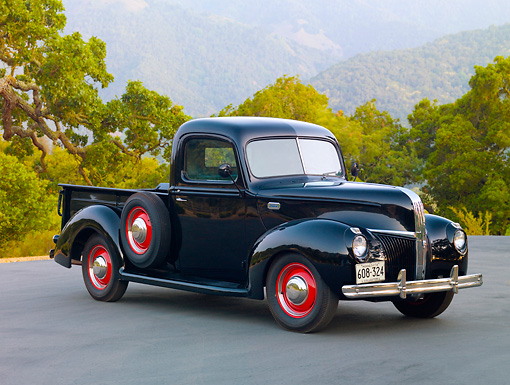 AUT 14 RK1565 01 © Kimball Stock 1941 Ford 1/2 Ton Pickup Truck Black 3/4 Front View On Pavement By Trees And Hills