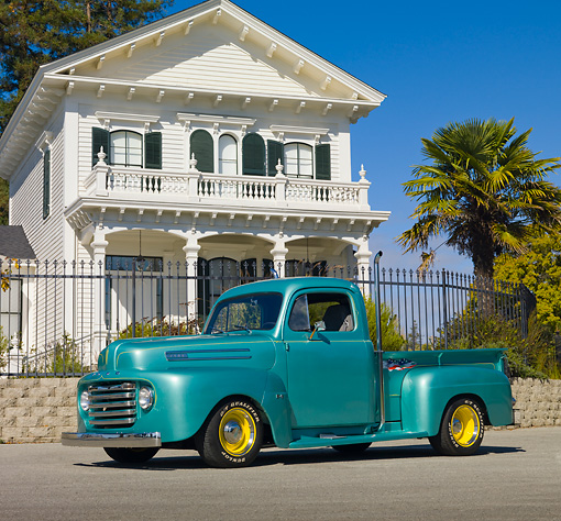 AUT 14 RK1577 01 © Kimball Stock 1950 Ford F1 Pickup Truck Green 3/4 Front View On Pavement By House