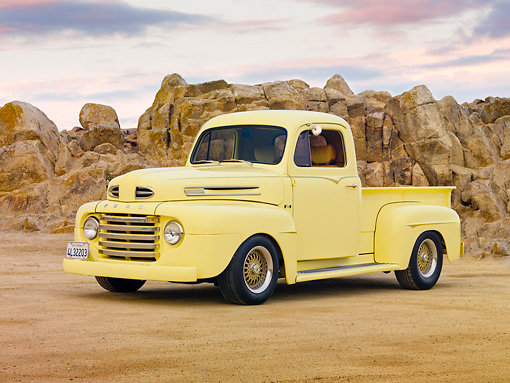 AUT 14 RK1585 01 © Kimball Stock 1949 Ford F-1 Pickup Truck Light Yellow On Sand By Boulders