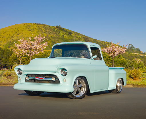 AUT 14 RK1616 01 © Kimball Stock 1957 Chevrolet Pickup Truck Pastel Aqua 3/4 Front View On Pavement By Cherry Blossom Trees