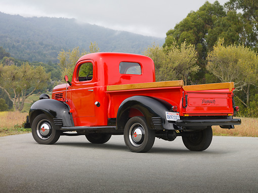 AUT 14 RK1622 01 © Kimball Stock 1939 Plymouth PT-81 Pickup Truck Red And Black 3/4 Rear View On Pavement By Trees And Fog