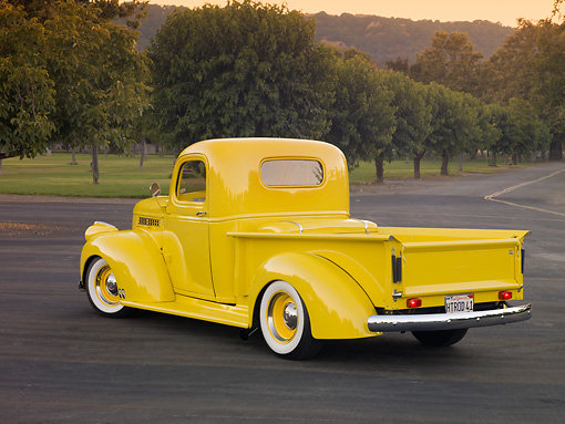 AUT 14 RK1633 01 © Kimball Stock 1941 Chevrolet Pickup Truck Yellow 3/4 Rear View On Pavement By Grass And Trees