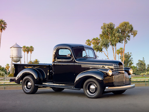 AUT 14 RK1641 01 © Kimball Stock 1946 Chevrolet Pickup Truck Black 3/4 Side View On Pavement By Trees And Water Tower