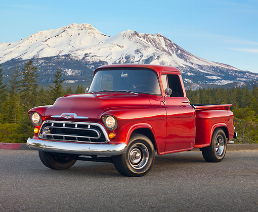 AUT 14 RK1654 01 © Kimball Stock 1957 Chevrolet 1/2 Ton Pickup Truck Red 3/4 Front View On Pavement By Trees And Mountains