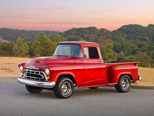 AUT 14 RK1658 01 © Kimball Stock 1957 Chevrolet 1/2 Ton Pickup Truck Red 3/4 Side View On Pavement By Field And Trees