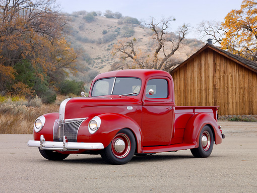 AUT 14 RK1677 01 © Kimball Stock 1941 Ford Pickup Truck Red 3/4 Front View On Pavement By Wooden Shed And Trees