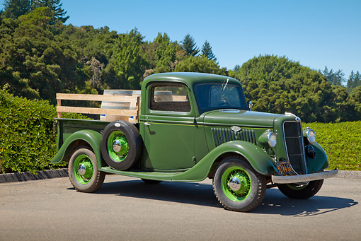 AUT 14 RK1705 01 © Kimball Stock 1935 Ford Pickup Green With Barrels 3/4 Side View On Pavement By Trees