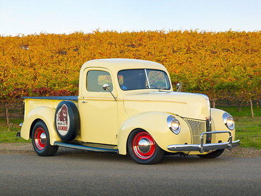 AUT 14 RK1731 01 © Kimball Stock 1941 Ford Pickup Yellow 3/4 Front View On Road By Vineyard