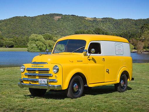 AUT 14 RK1752 01 © Kimball Stock 1948 Dodge Panel Truck Yellow With White Stripe 3/4 Front View On Grass By Pond