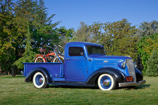 AUT 14 RK1757 01 © Kimball Stock 1937 Chevrolet Pickup Blue And Black With Bicycles 3/4 Side View On Grass By Trees