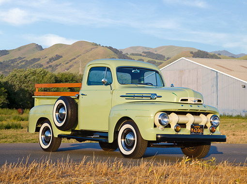 AUT 14 RK1769 01 © Kimball Stock 1952 Ford F-1 Pickup Glen Mist Green 3/4 Front View On Pavement By Shed And Grassy Hills