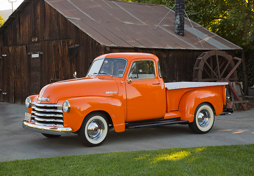 AUT 14 RK1789 01 © Kimball Stock 1953 Chevrolet Pickup Orange 3/4 Side View On Pavement By Wooden Shed