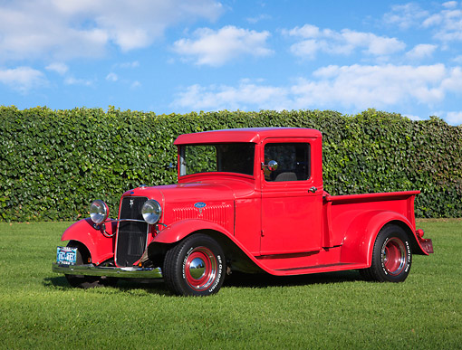 AUT 14 RK1790 01 © Kimball Stock 1934 Ford Pickup Red 3/4 Front View On Grass By Shrubs