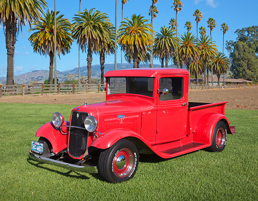 AUT 14 RK1791 01 © Kimball Stock 1934 Ford Pickup Red 3/4 Front View On Grass By Palm Tree