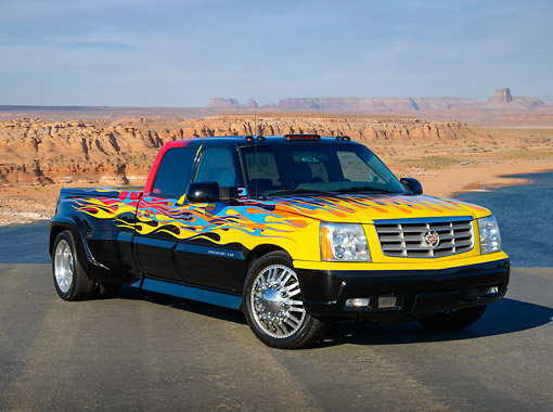 AUT 14 RK1800 01 © Kimball Stock 2006 Cadillac Escalade XXL Black With Yellow, Blue And Red Flames 3/4 Front View On Pavement In Desert