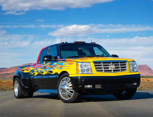 AUT 14 RK1801 01 © Kimball Stock 2006 Cadillac Escalade XXL Black With Yellow, Blue And Red Flames 3/4 Front View On Pavement In Desert