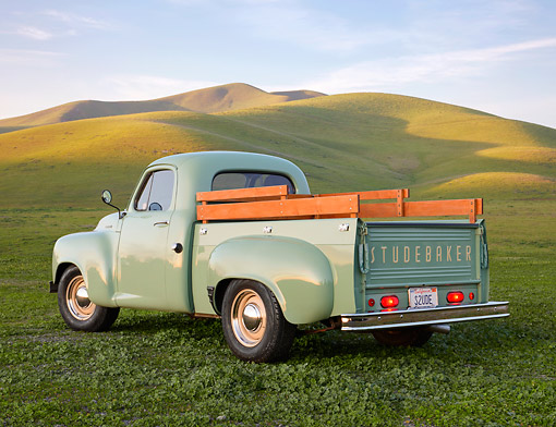 AUT 14 RK1806 01 © Kimball Stock 1949 Studebaker 2R5 Pickup Green 3/4 Rear View On Grass By Hills