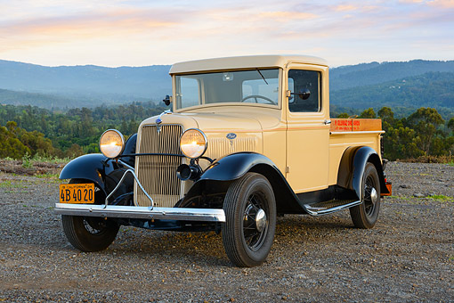 AUT 14 RK1808 01 © Kimball Stock 1934 Ford Pickup Tan And Black 3/4 Front View On Gravel By Hills