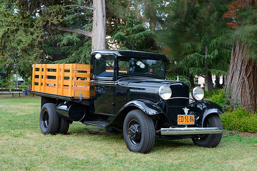 AUT 14 RK1816 01 © Kimball Stock 1932 Ford 1 1/2 Ton Stakebed Pickup Black 3/4 Front View On Grass By Trees