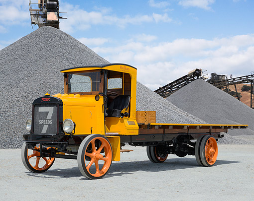 AUT 14 RK1836 01 © Kimball Stock 1920 Fageol 7 Speed Yellow And Black 3/4 Front View On Pavement By Gravel Piles