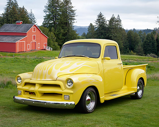 AUT 14 RK1856 01 © Kimball Stock 1954 Chevrolet Pickup Yellow With Flames 3/4 Front View On Grass By Red Barn