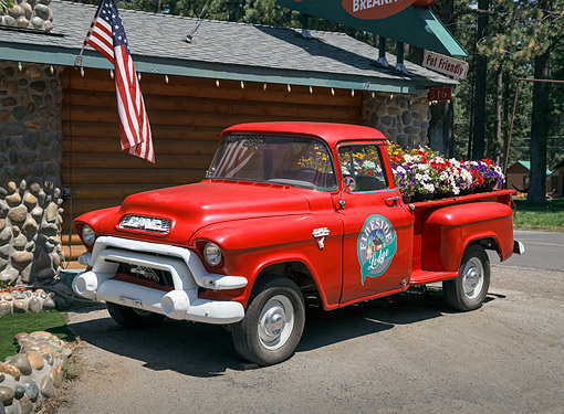AUT 14 RK1861 01 © Kimball Stock 1956 GMC Pickup Truck Red With Flowers 3/4 Front View On Gravel By Lodge
