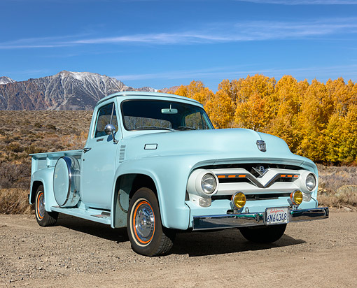 AUT 14 RK1869 01 © Kimball Stock 1955 Ford F-350 Light Blue 3/4 Front View On Gravel By Mountains And Autumn Trees