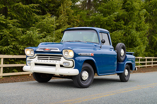 AUT 14 RK1876 01 © Kimball Stock 1959 Chevrolet 3100 Apache Pickup Truck Blue 3/4 Front View On Road By Fence And Evergreen Trees