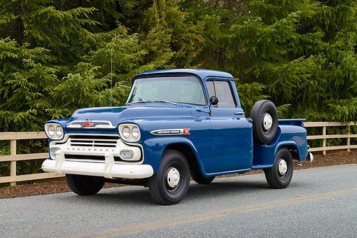 AUT 14 RK1877 01 © Kimball Stock 1959 Chevrolet 3100 Apache Pickup Truck Blue 3/4 Front View On Road By Fence And Evergreen Trees