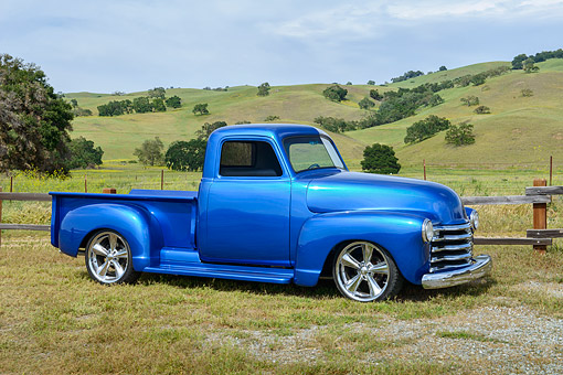 AUT 14 RK1878 01 © Kimball Stock 1951 Chevrolet 3100 Pickup Truck Blue 3/4 Side View On Grass By Hills
