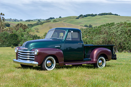 AUT 14 RK1884 01 © Kimball Stock 1952 Chevrolet 3100 Pickup Truck Green And Brown 3/4 Side View On Grass By Hills