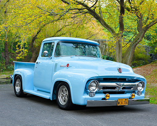 AUT 14 RK1931 01 © Kimball Stock 1956 Ford F-100 Pickup Blue 3/4 Front View On Pavement By Trees