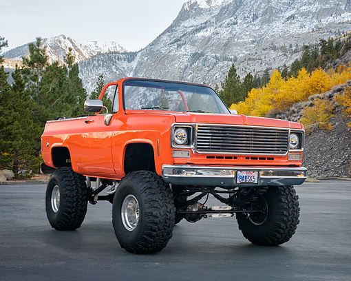 AUT 14 RK2006 01 © Kimball Stock 1975 Chevrolet Pickup Orange Custom Lifted 3/4 Front View By Trees And Mountains