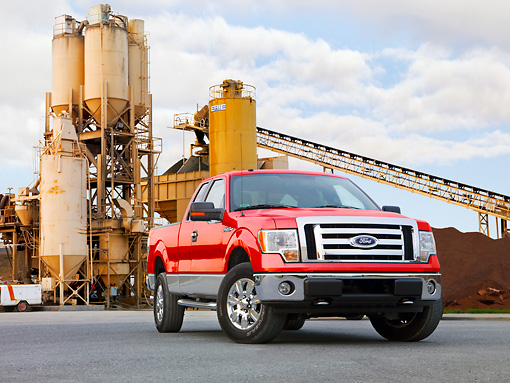 AUT 14 BK0014 01 © Kimball Stock 2009 Ford F-150 Supercab XLT Pickup Truck Red 3/4 Front View On Pavement By Plant