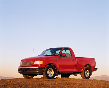 AUT 14 RK0036 03 © Kimball Stock 1999 Ford F150 Lariat with Triton V8 Red 3/4 Side View On Dirt Hill Blue Sky