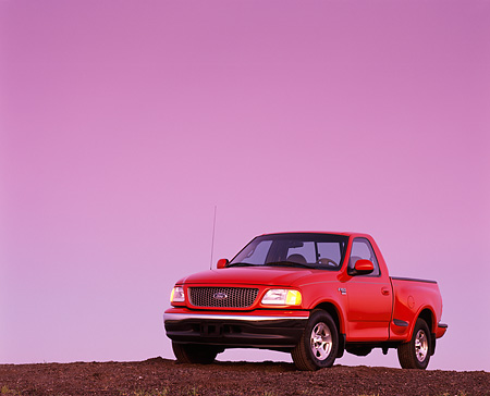 AUT 14 RK0039 03 © Kimball Stock 1999 Ford F150 Lariat with Triton V8 Red 3/4 Front View On Dirt Hill At Dusk