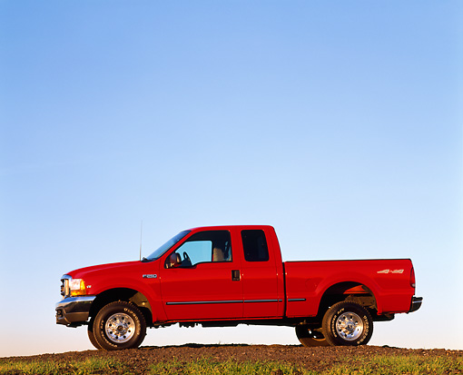 AUT 14 RK0041 01 © Kimball Stock 1999 Ford F250 XLT Super Duty 4x4 with Triton V10 Red Profile View On Dirt