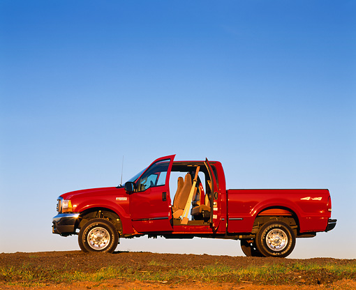 AUT 14 RK0042 03 © Kimball Stock 1999 Ford F250 XLT Super Duty Red 4x4 Triton V10 Quad Door Profile View Doors Open On Dirt Hill Blue Sky