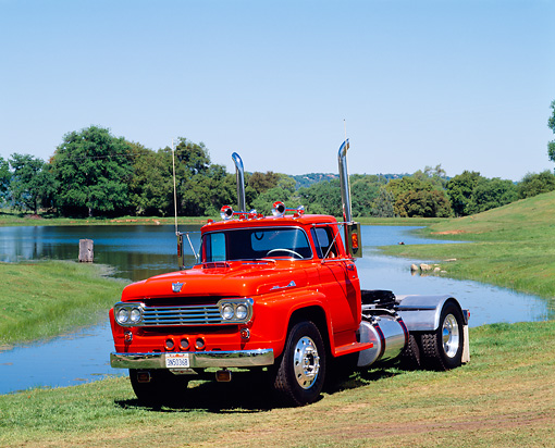 AUT 14 RK0084 07 © Kimball Stock 1959 Ford F-9000 Semi Truck Orange 3/4 Front View On Grass By Lake