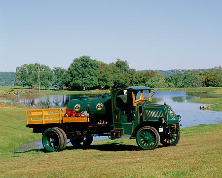 AUT 14 RK0091 03 © Kimball Stock 1919 Mack AC Stake Truck Green 3/4 Front View On Grass Hill By Water