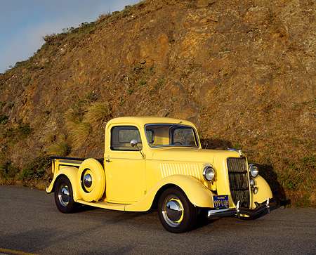 AUT 14 RK0097 08 © Kimball Stock 1936 Ford 327 Truck Yellow Side 3/4 Front View On Pavement Against Rock
